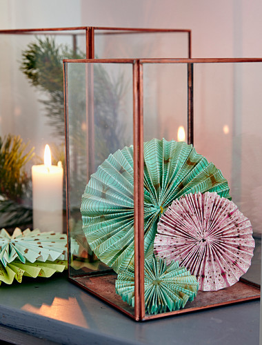 Christmas arrangement of rosettes made from patterned paper in candle lantern