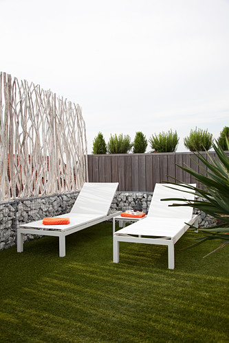 Two white loungers next to screen made from branches and gabions