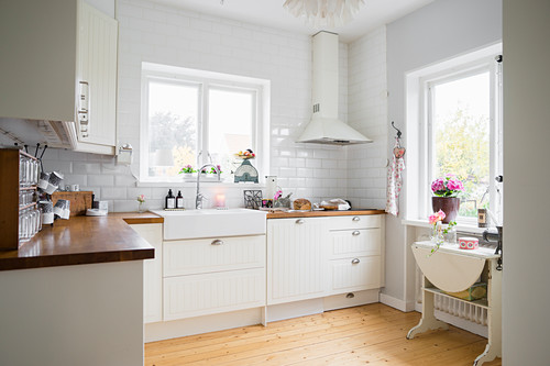 Tiled wall and window in white fitted kitchen