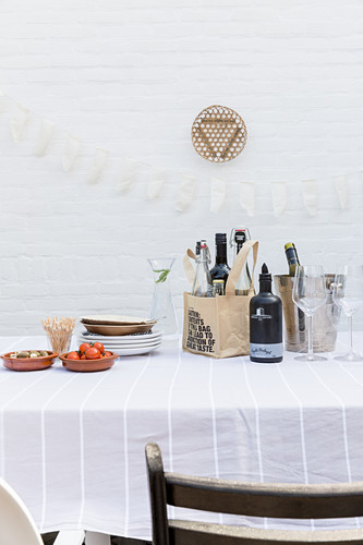 Ingredients for starters and drinks on table against white wall on terrace