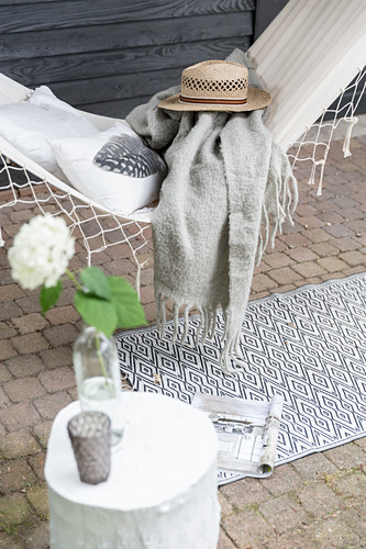 Cushion, blanket and hat on hammock on veranda