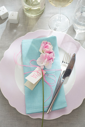 Place setting with pale blue linen napkin, flower and name card