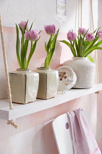 Tulips in ceramic vases on shelves