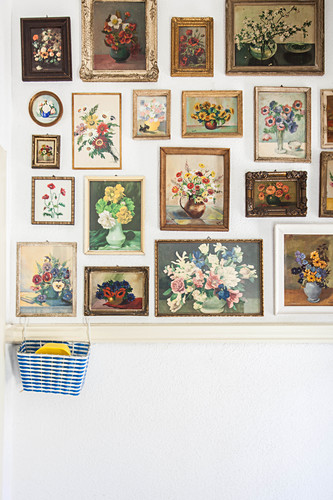 Gallery of framed, floral still-life paintings on white wall