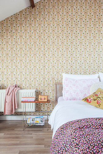 Double bed in attic bedroom with retro wallpaper