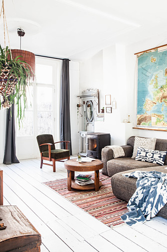 Antique wardrobe, log burner, armchair with green upholstery, sofa set and coffee table in living room with white wooden floor and terrace doors