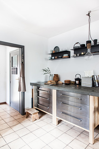Base units with drawers and concrete worksurface below black wall-mounted shelves in kitchen