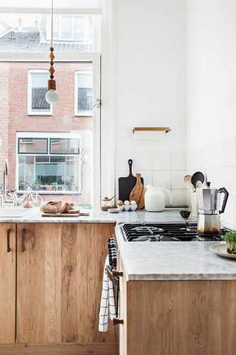 Simple kitchen in natural shades with wooden cabinets and marble worksurfaces