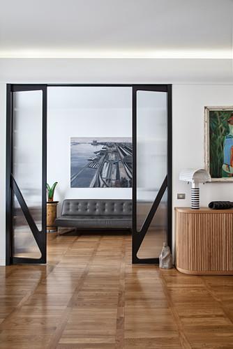 Grey leather sofa seen through sliding doors