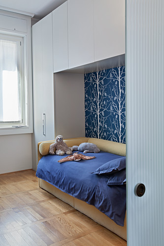 Fitted cupboards above and surrounding bed in child's bedroom