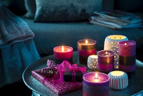 Violette Kerzen, Windlichter und Geschenke auf dunklem Couchtisch