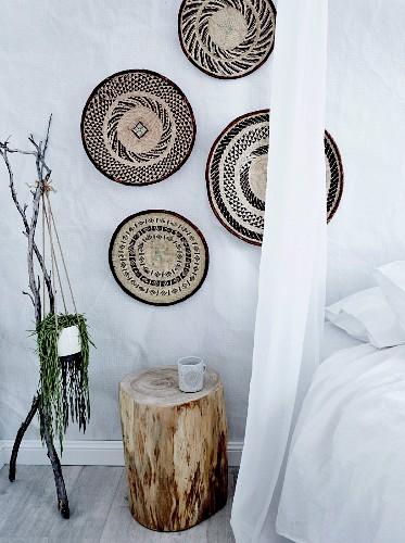 Wanddeko aus Korbschalen über Baumstamm als Nachttisch