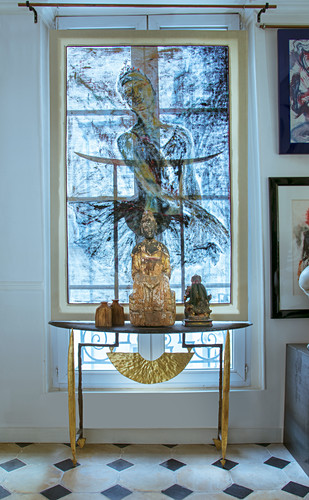 Buddha figurine on console table in front of window with painted translucent roller blind