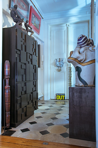 Cabinet with structured front and collection of sculptures in foyer