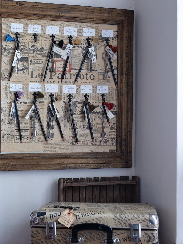 Key hooks in wooden frame lined with old French newspapers