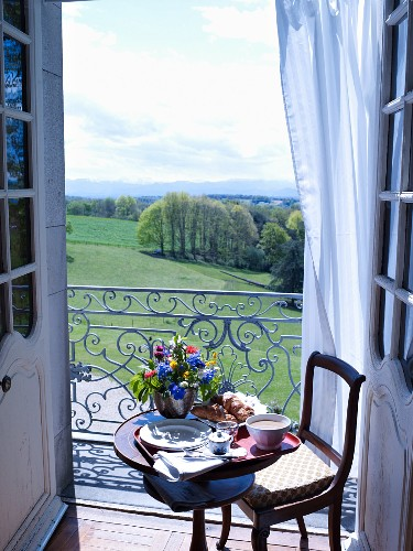 Small table set for breakfast with vase of flowers in front of balcony with a view