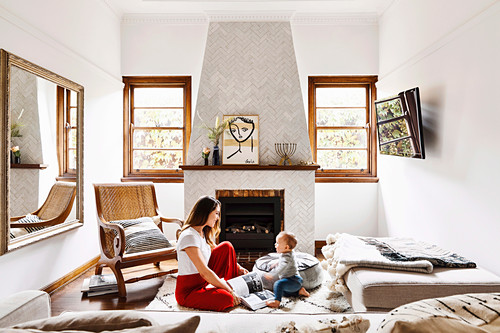 Woman and toddler on the floor in the living room in earth tones