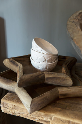 White bowls with relief patterns on two star-shaped wooden trays