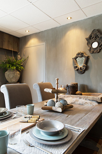 Table set in natural shades in dining room with grey glazed walls