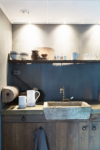 Stone sink below cups on shelf in rustic country-house kitchen
