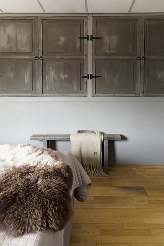 Fitted, wall-mounted cupboards with rustic doors in bedroom