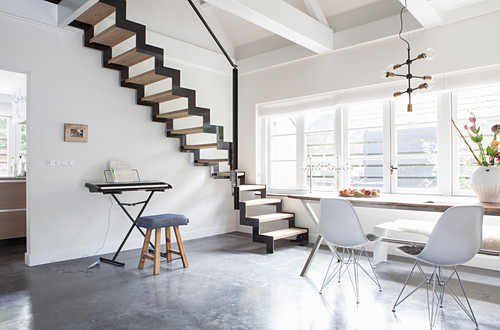 Dining table, classic chair and keyboard below zigzag staircase in open-plan interior with concrete floor