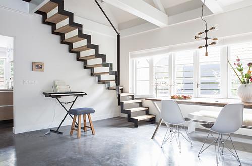 Esstisch mit Klassikerstühlen und Klavier vor Zick-Zack-Treppe in offenem Wohnraum mit Betonboden