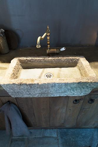 Rustic stone sink in dark kitchen