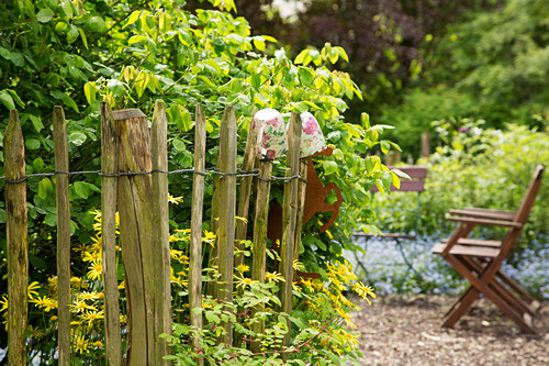 Chestnut paling fence next to garden chairs on gravel terrace