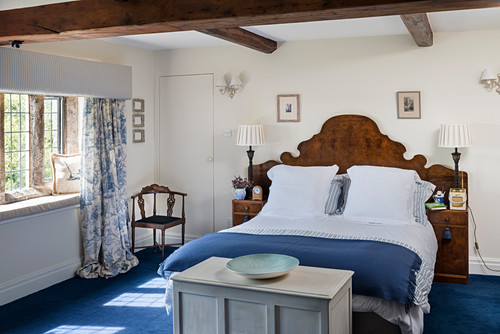 Double bed with antique wooden headboard in blue and white bedroom