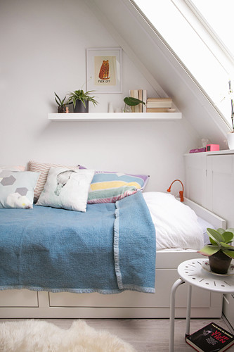 Blue blanket on bed with drawers below under sloping ceiling