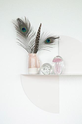 Feathers in jug on artistic metal shelf