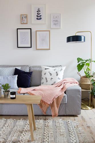 Graues Sofa neben Stehlampe und Zimmerpflanze im Wohnzimmer