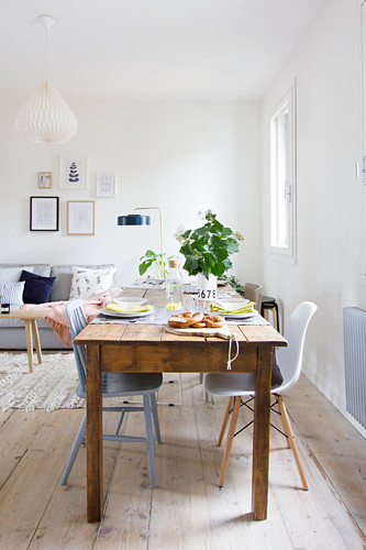 Alter Holztisch mit Stühlen im Wohnzimmer mit weißen Wänden und Holzdielenboden