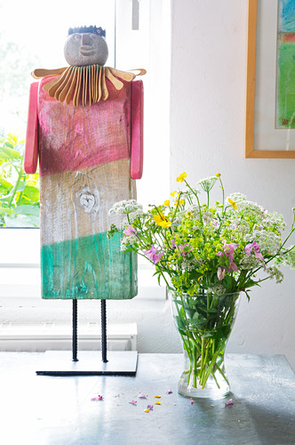 Pastel wooden sculptures next to bouquet of wildflowers