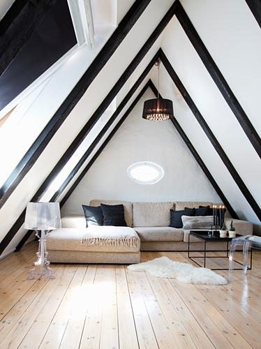 Elegant attic living room with black ceiling beams