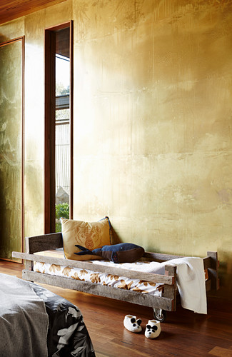 Cot in front of a wall with patinated brass cladding
