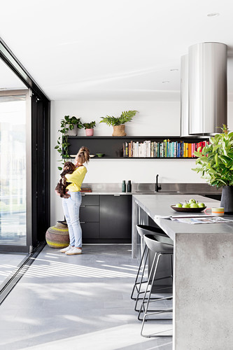 Woman and dog stand in modern kitchen with concrete island