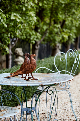 Rusty pheasant figures on a metal table in the garden