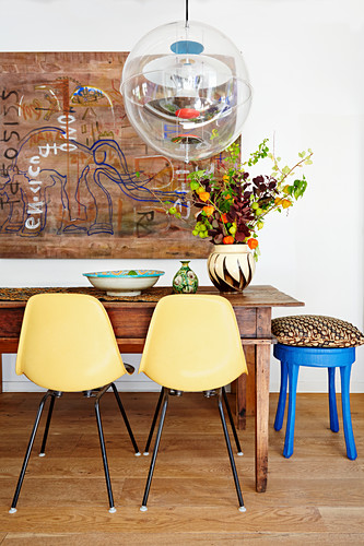 Shell chairs and transparent spherical lamp in ethnic dining room