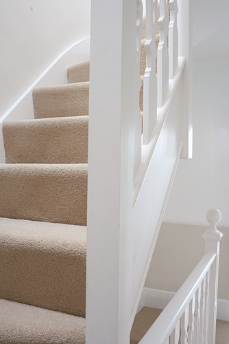 Staircase with newly laid beige carpet