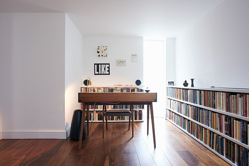 Desk in front of narrow, floor-to-ceiling window and next to long, low bookcase
