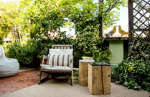 Two wooden blocks used as side tables next to armchair on terrace