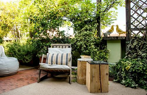 Zwei Holzklötze als Beistelltisch neben einem Sessel auf der Terrasse