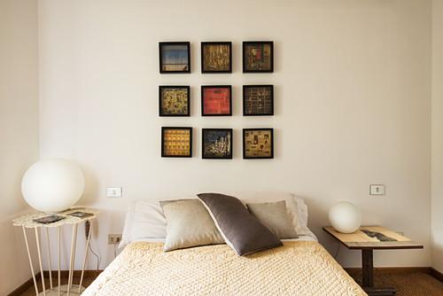Zum Quadrat angeordnete Bilder über dem Bett