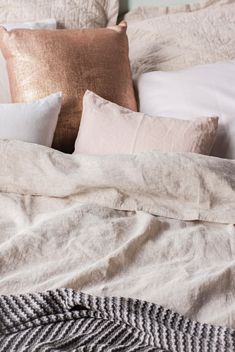 Champagne-colored pillows on the bed with linen bedding