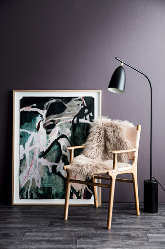 Scandinavian chair with sheepskin in front of painting and purple wall