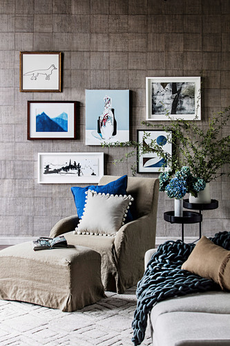 Armchairs and ottoman with linen cover in front of picture gallery on wall with designer wallpaper