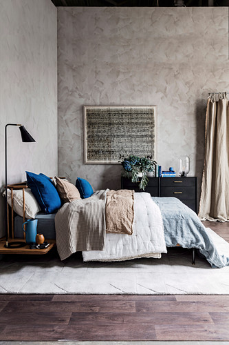 Schlafzimmer mit blauen und erdfarbenen Accessoires