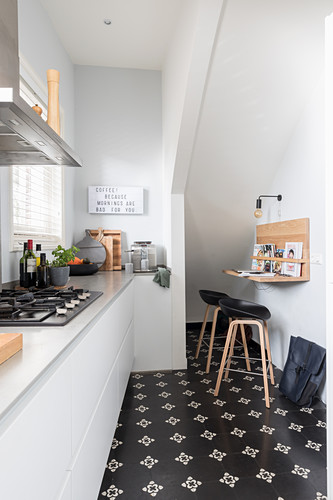 White fitted kitchen and small breakfast bar with bar stools under staircase